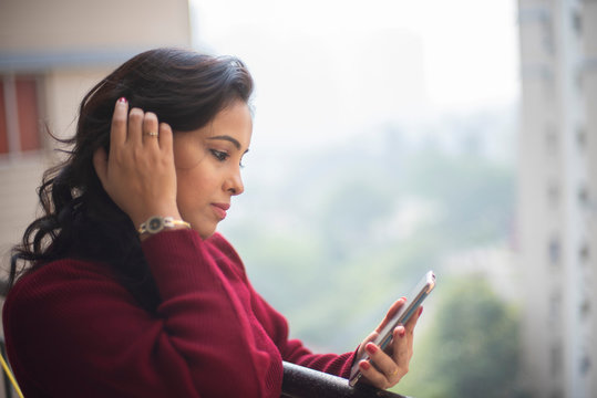 An young and attractive brunette Indian Bengali woman in maroon western woolen high neck sweater standing on a balcony with phone in urban  background. Indian lifestyle and Christmas celebration.
