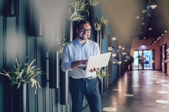 Half length portrait of successful boss using netbook technology with 4g wireless internet connection in workspace interior, prosperous employee in classic eyewear holding laptop computer and smiling