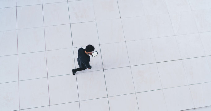 Man walking on white floor and using tablet