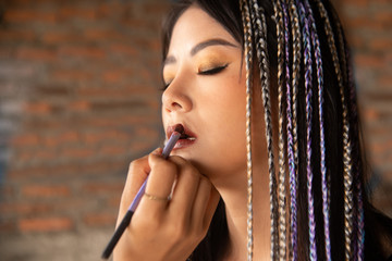 Makeup artist writing lip for young Asian woman.