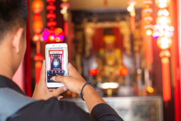 Tourist using mobile phone screen for picture with smartphone of temple in Asia tourism travel. People taking photos during vacation.
