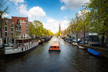 Amsterdam canal with cruise ship with Netherlands traditional house in Amsterdam, Netherlands. Landscape and culture travel, or historical building and sightseeing concept.