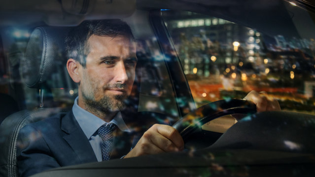 An young handsome businessman driving a modern car in center of the city by night. Concept of business, success, traveling, luxury