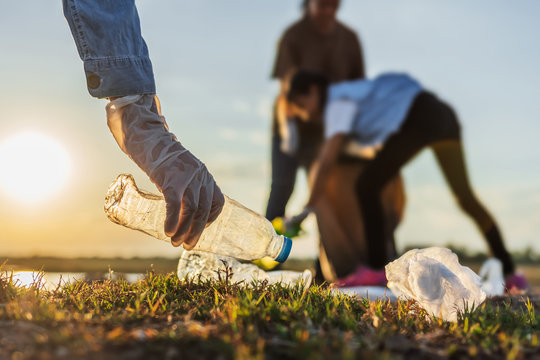 people volunteer keeping garbage plastic bottle into black bag at park river in sunset