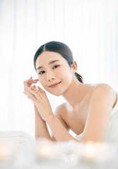 Closeup beautiful asian young woman applying lotion to arm shoulder skin at Asian luxury spa and wellness. Portrait of beauty woman relaxing in beauty clinic, healthcare lifestyle concept
