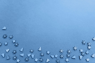 Small wooden Christmas trees and snowflakes in classic blue color.