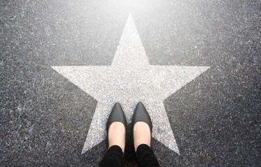 Success in business design concept. Businesswoman standing on street road background. Top view. Selfie of feet in black high heels shoes and white star symbol on pathway floor. New talent or champion.