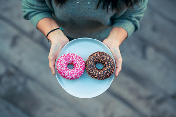 Woman holding a plate with delicious and colored donuts