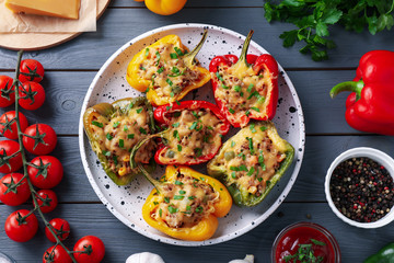 Flat lay composition with tasty stuffed bell peppers on grey wooden table