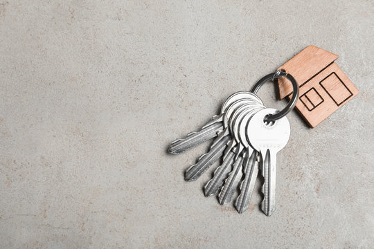 Keys with trinket in shape of house on grey stone background, top view and space for text. Real estate agent services