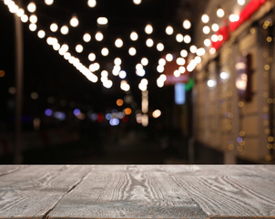 Empty wooden surface and blurred view of night street decorated for Christmas. Bokeh effect