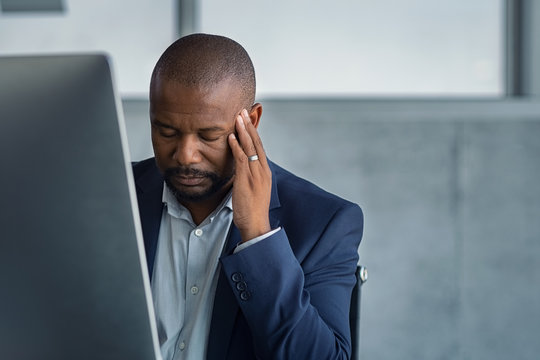 Stressed mature businessman working at office