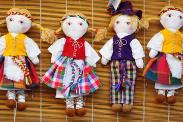 Cute handmade ragdoll dolls in Lithuanian national costumes sold on Easter market in Vilnius, Lithuania