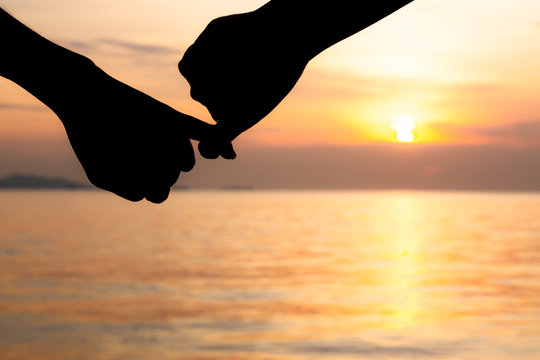 Silhouette of hand to pinky promise, pinky swear in front of the sun during sunset time. Love and valentine concept.