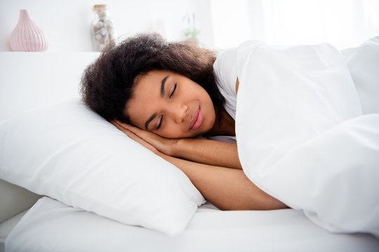 Profile photo of charming curly dark skin lady lying sheets bed covered white blanket hold hands under head eyes closed weekend saturday morning wear pajama room indoors