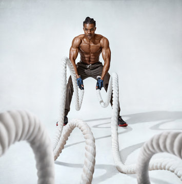 Muscular man working out with heavy ropes. Photo of handsome man with perfect body on grey background. Strength and motivation. Full length