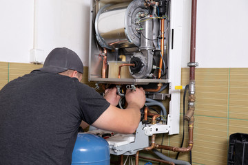 plumber fixing central heating system, Worker servicing a gas boiler