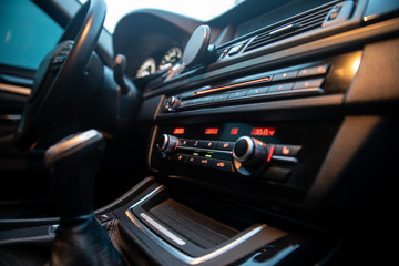 Car interior close-up. Dashboard lights on. Selective focus points.