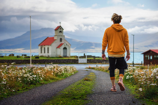 Young man walking towards a church and a cemetery in Iceland