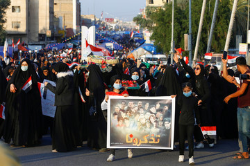 Iraqi demonstrators women carry pictures of people who were killed during ongoing anti-government protests in Nassiriya