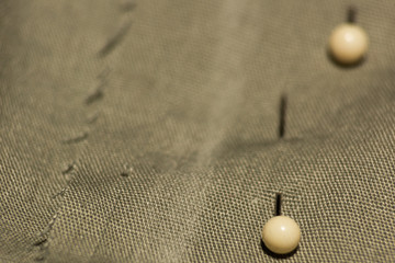 White pins with balls stuck in a fabric