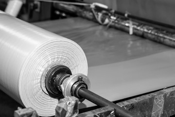 Black & White imagery of spool of plastic packaging sheet heavy duty for industrial use outdoors. wrapped around a metal pole ready to feed into a machine for cutting into shape or printing logos.