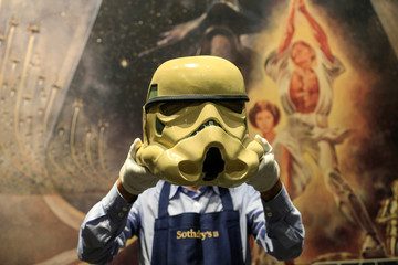 "A Sotheby's employee poses with a prototype of an Imperial Stormtrooper helmet 1976, estimated at £30,000-£60,000 created for the first ""Star Wars"" film during a photocall at Sotheby's in London"