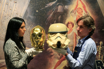 "A Sotheby's employee holds a ""Return of the Jedi"" promotional C-3PO Helmet 1983, estimated at £15,000-£25,000 created by George Lucas' visual effects company during a photocall at Sotheby's in London"