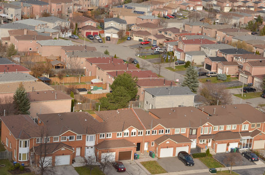 Ariel view of rooftops of north american neighborhood town houses . Rows of houses with empty street can be seen here.