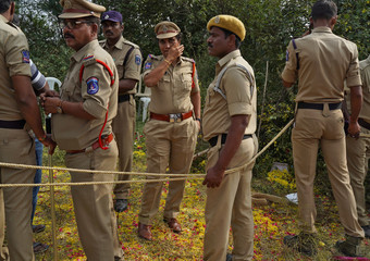 Police officers stand at the site where police shot dead four men suspected of raping and killing a 27-year-old veterinarian, in Chatanpally on the outskirts of Shadnagar