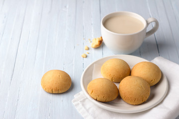 Homemade gluten free cottage cheese rice cookies and cup of tea with milk on light background