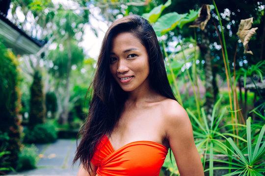 Asian touristic woman walking amid tropical plants