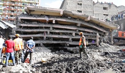 People watch as rescue teams search the scene where a building collapsed in Nairobi