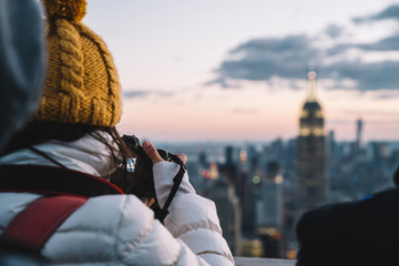 Back view of traveler in winter clothes taking photo of skyscrapers in skyline at evening time exploring New York city during holidays. Sightseeng to Famous Empire State Building Landmark