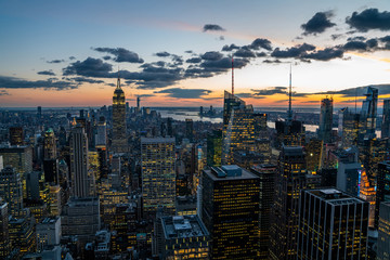 Fotomurales - Aerial view of skyscrapers and towers in midtown skyline of Manhattan with evening sunset sky. Scenery cityscape of financial district with famous New York Landmark, illuminated Empire State Building