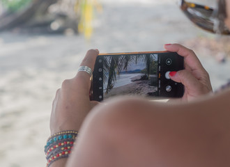 Woman takes a picture of a tropical beach with her cellphone