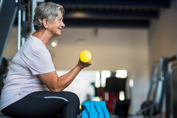 mature woman at the gym training her body and her biceps sitting in a bench with a dumbbell in her hand - healthy and fitness senior lifestyle Wall mural
