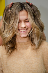 Portrait of Beautiful caucasian smiling woman after coloring hair. Hairstylist puts fingers into models hair and makes her laugh. AirTouch technique