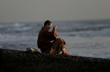 A nun takes pictures with a mobile phone of the sunset on a beach in Colombo