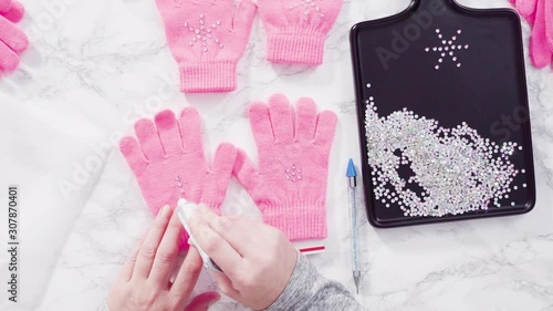 Wall mural Flat lay. Rhinestone pink kids gloves with snowflake shapes.