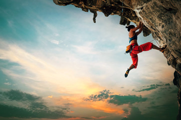 Athletic Woman climbing on overhanging cliff rock with sunset sky background.