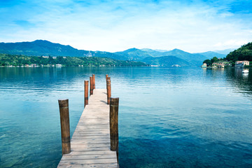 Wooden pier on Orta San Giulio Lake with greenery mountain background. Italy.