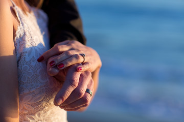 Isolated picture of Bride and grooms hands showing rings