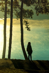 younger woman standing beside beautiful highland lake in northern of thailand