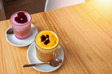 Fotobehang - Pink and yellow colorful latte drink decorated with flowers.