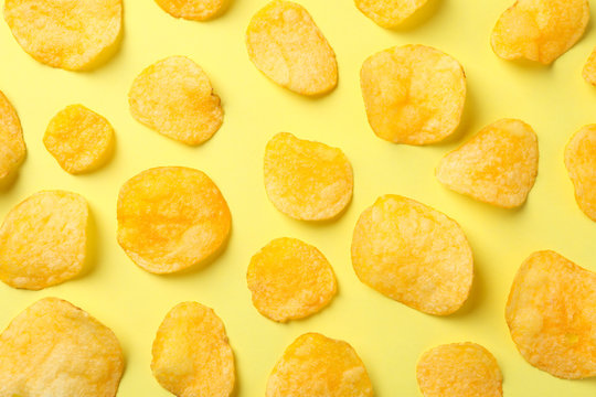Flat lay composition with potato chips on yellow background, top view