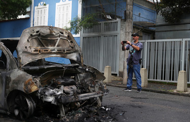 A police officer takes a picture of a car that was set on fire before dawn in the Rio Comprido neighborhood of Rio de Janeiro