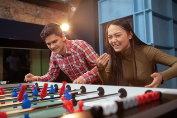 Young happy multiethnic couple having fun together, playing table soccer