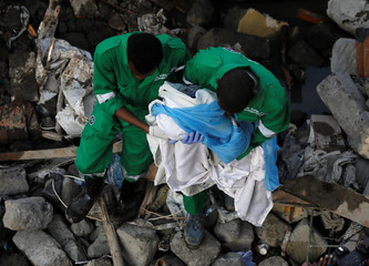Rescuers carry a dead infant found in the rubble at the scene where a building collapsed in Nairobi