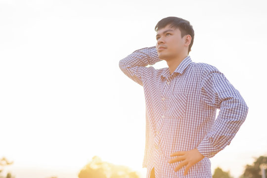 Portrait of a handsome young farmer standing in a natural background shirt at sunset